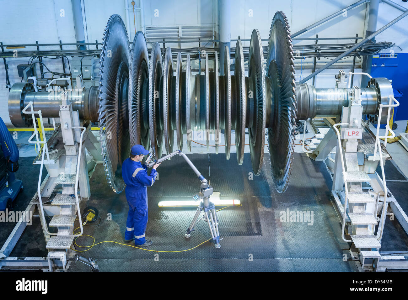 Engineer measuring low pressure steam turbine parts in repair works - Stock Image