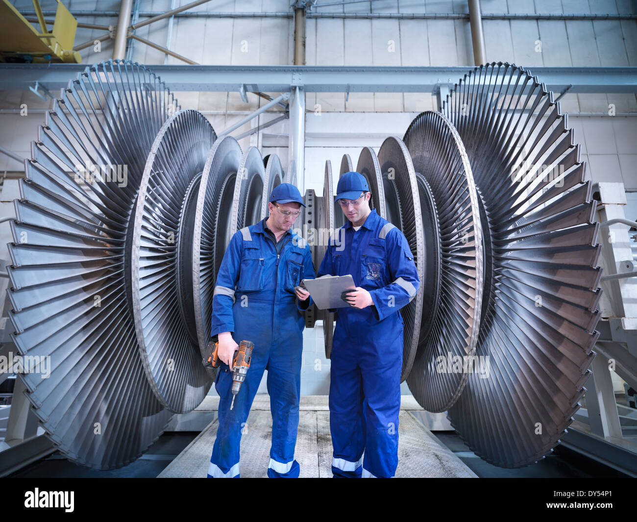 Engineers discussing notes in front of steam turbine in workshop - Stock Image