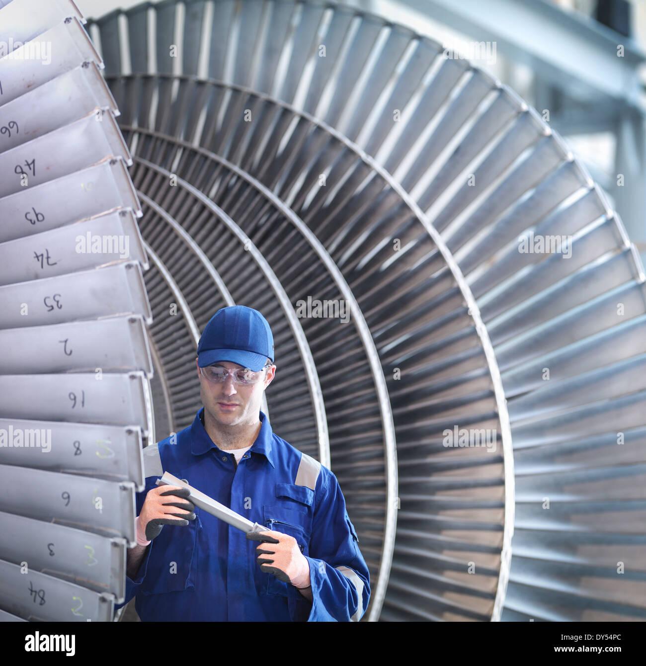 Engineer inspecting steam turbine blade in workshop - Stock Image