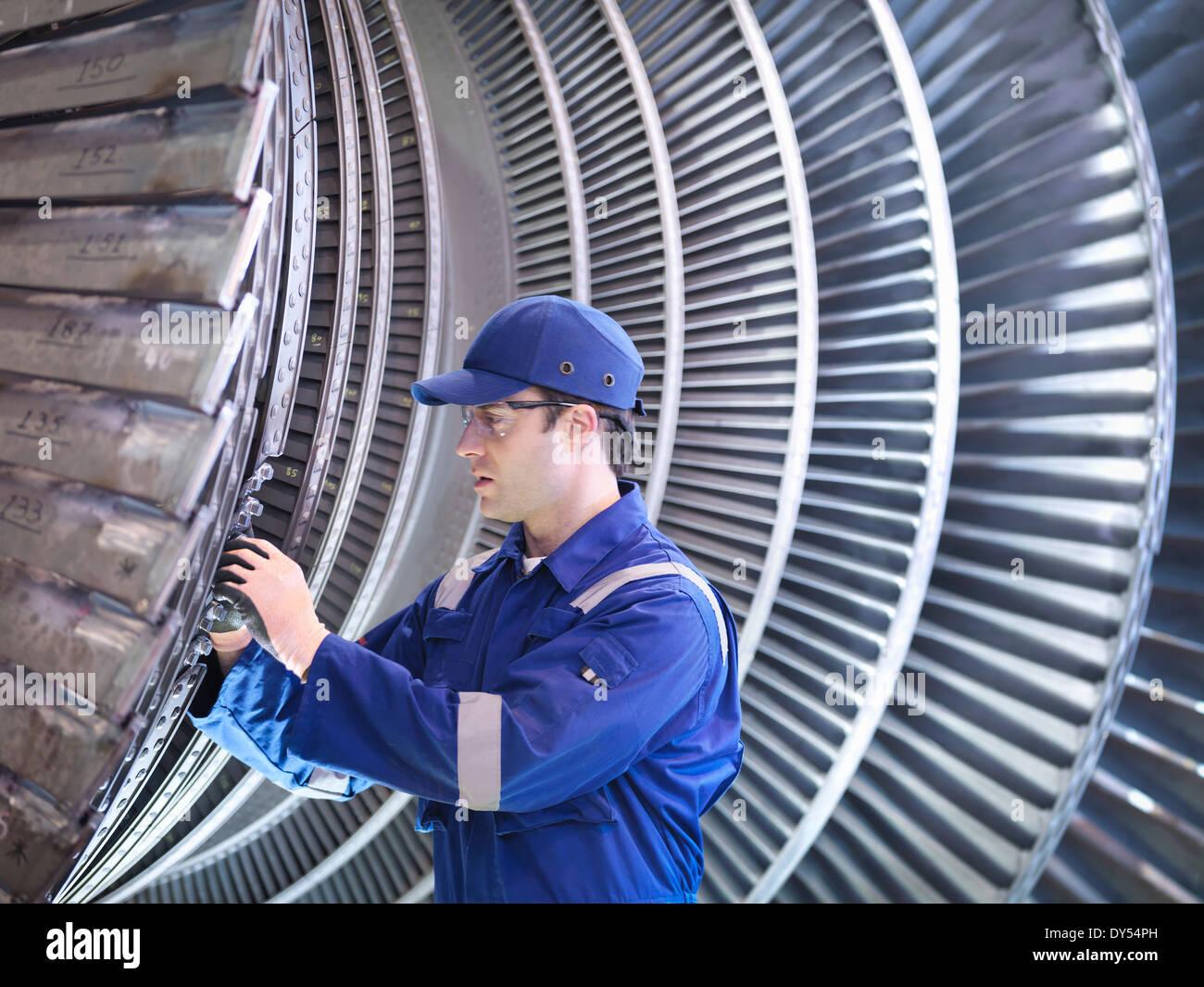 Engineer inspecting repair to steam turbine blade in workshop - Stock Image