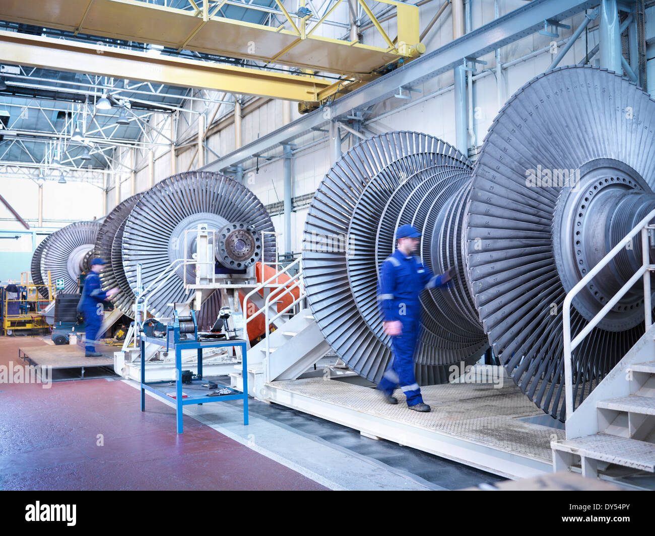 Engineers with low pressure steam turbines in repair bays in workshop - Stock Image