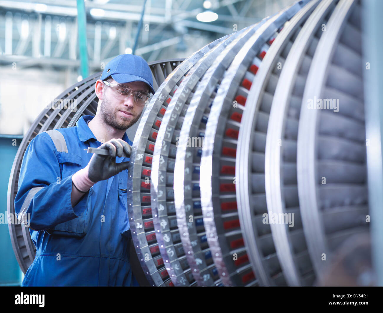 Engineer measuring high pressure steam turbine blade in workshop - Stock Image