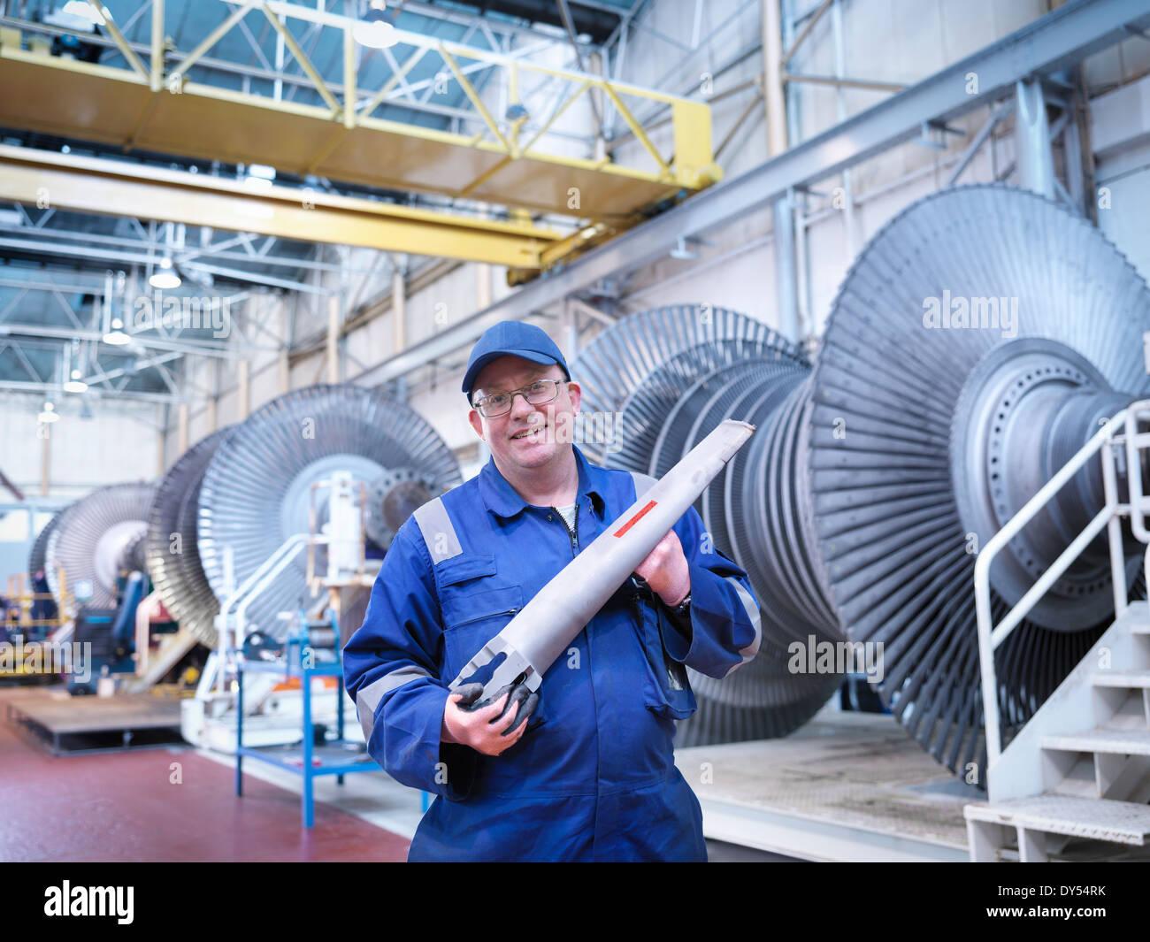 Portrait of engineer holding rotor blade in turbine repair workshop - Stock Image
