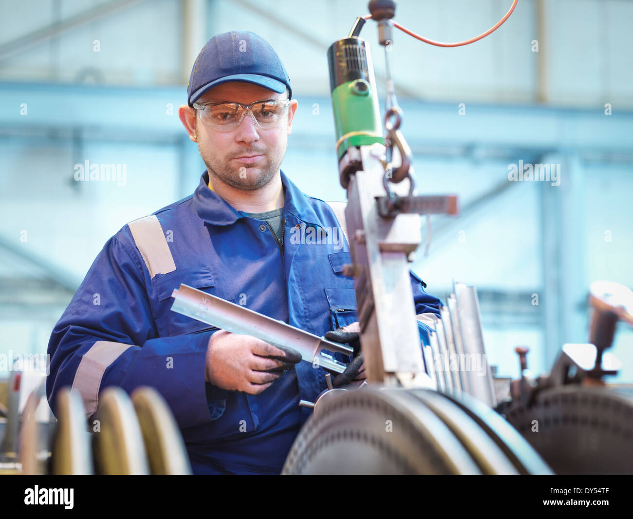 Portrait of engineer fitting blades to steam turbine in repair works - Stock Image