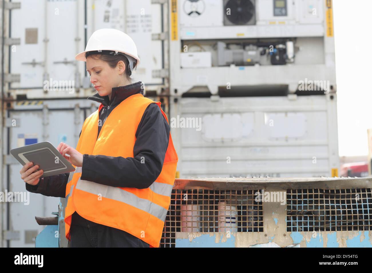 Female dockworker using monitor - Stock Image