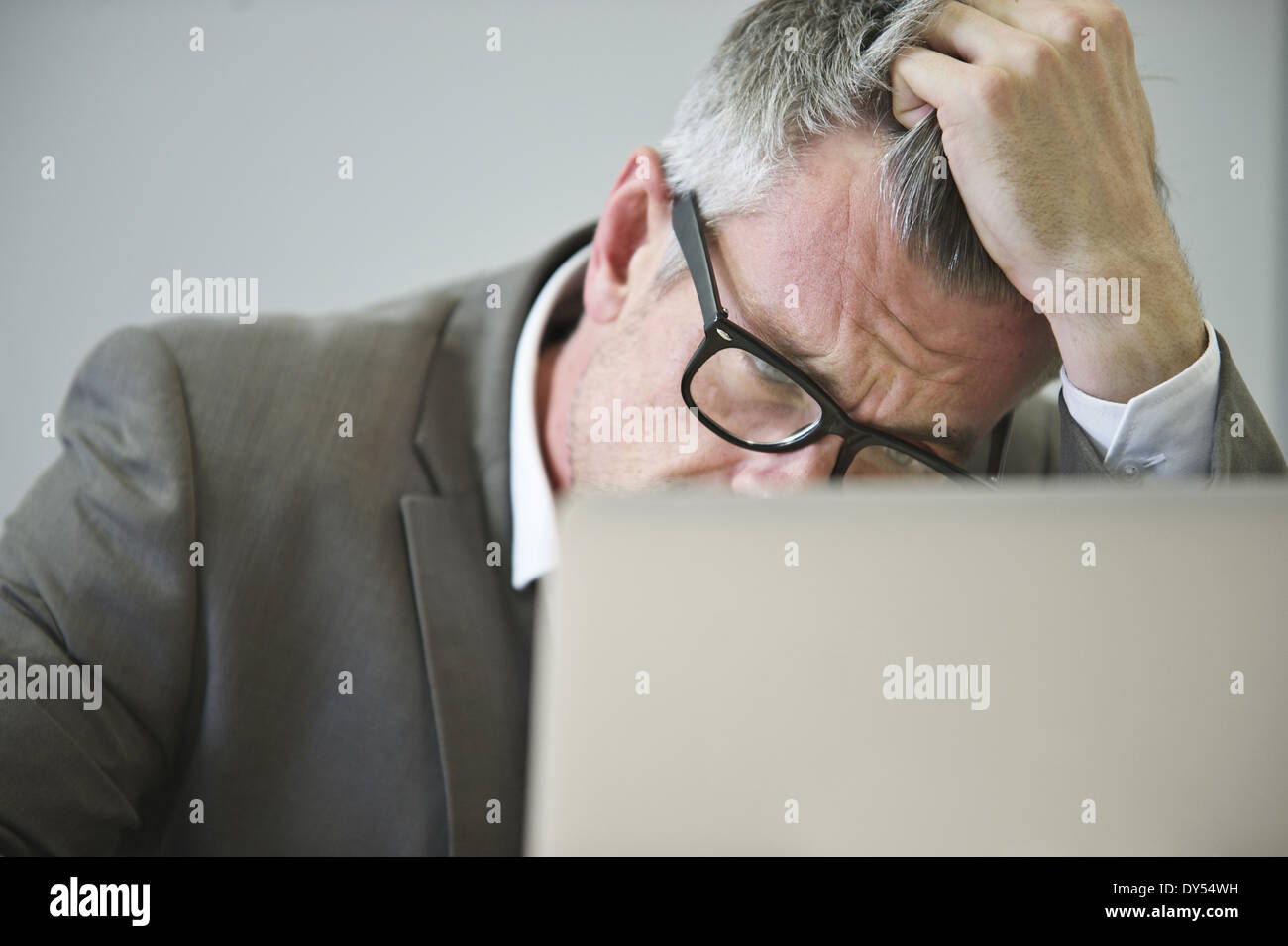 Stressed mature businessman in office - Stock Image