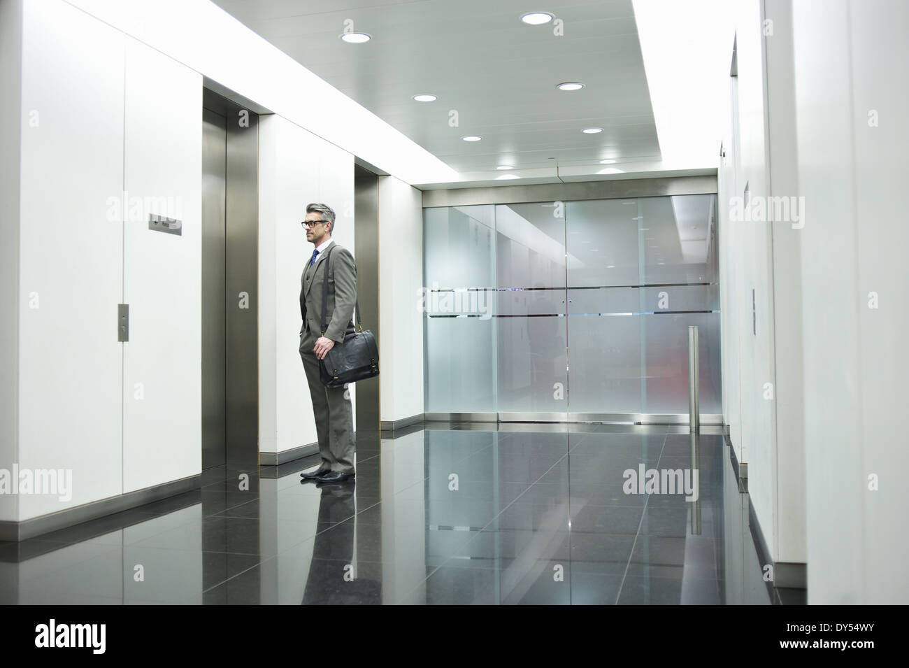 Businessman waiting for elevator in office corridor - Stock Image