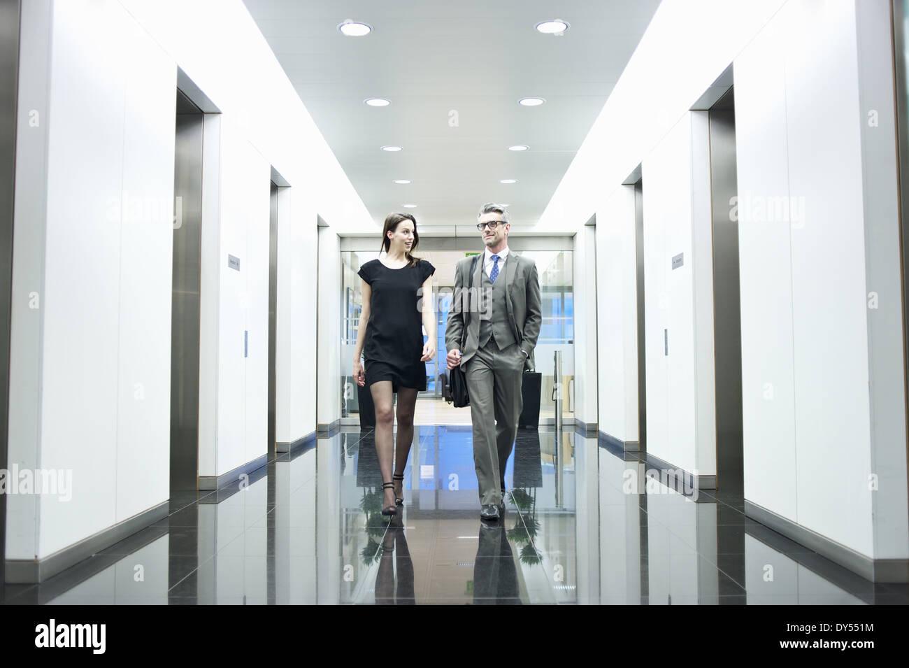 Business partners walking along office corridor - Stock Image