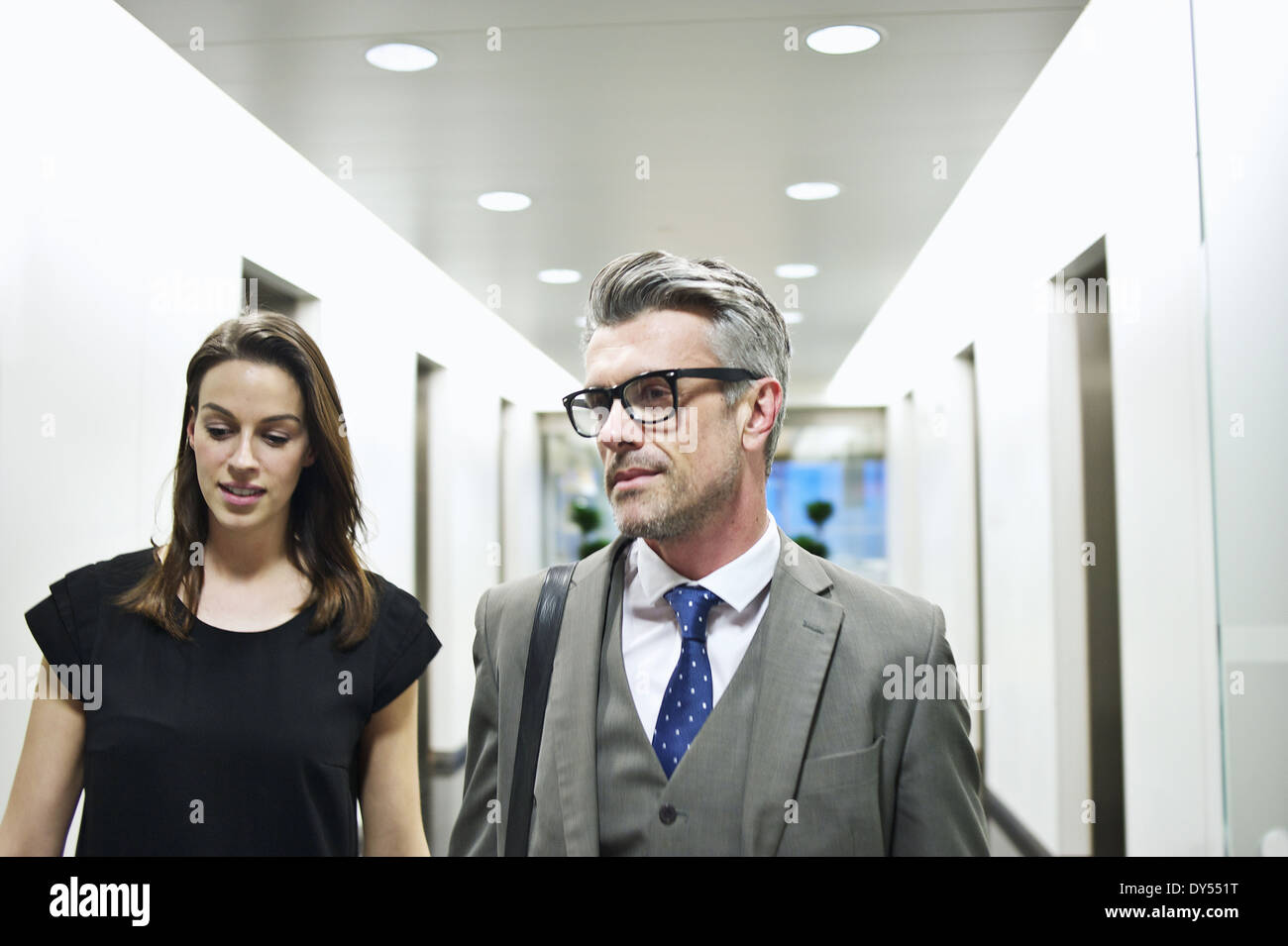 Business colleagues walking along office corridor - Stock Image