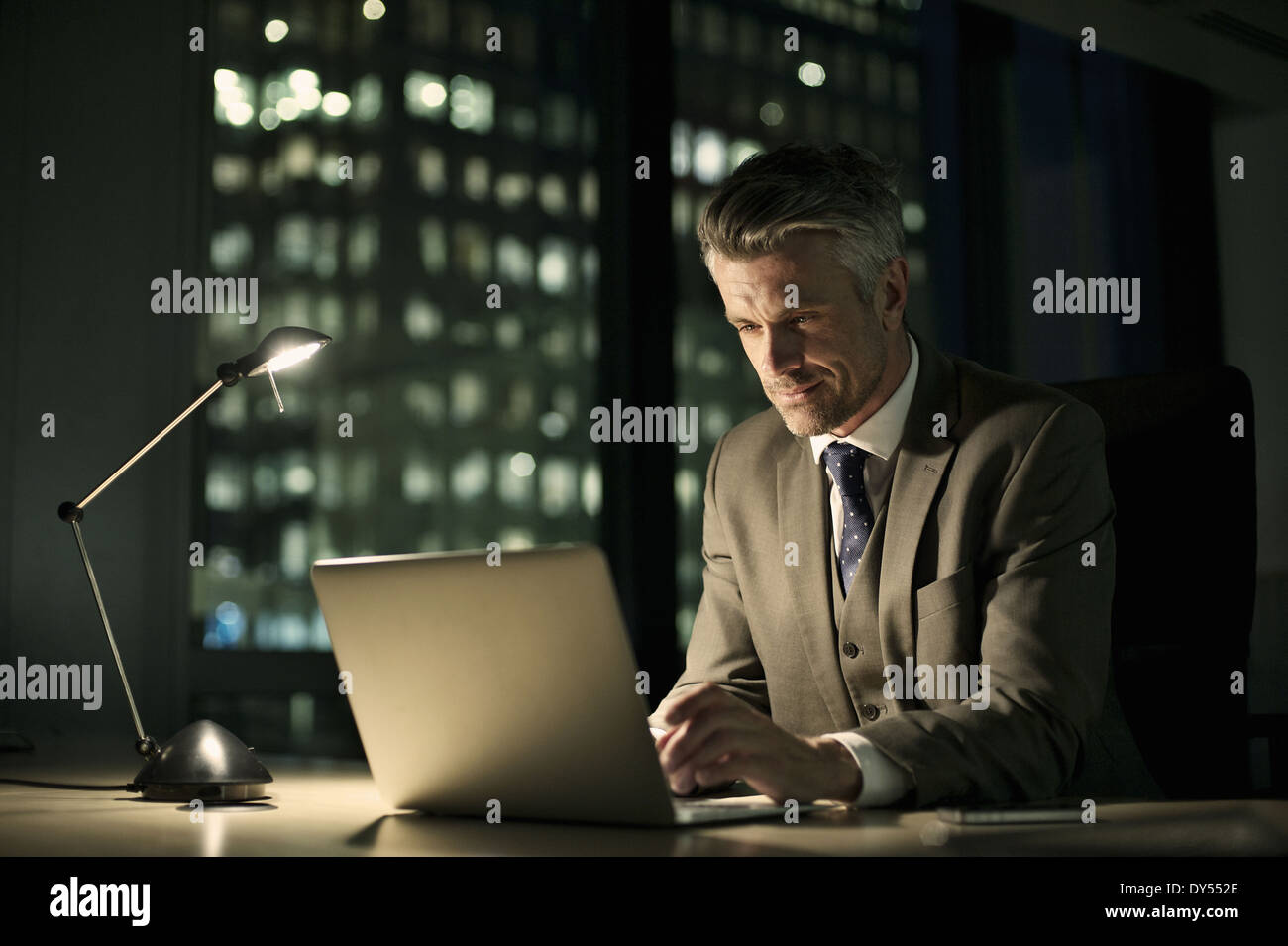 Businessman working late in office on laptop - Stock Image