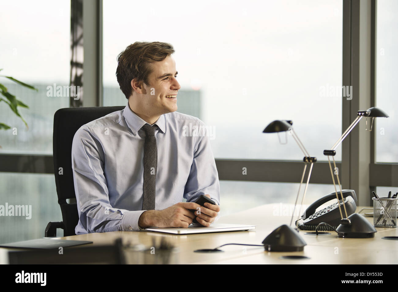 Young businessman sitting at desk in office - Stock Image