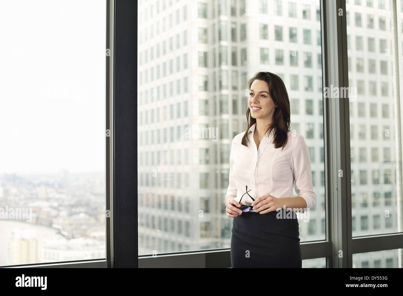 Portrait of young businesswoman looking out of office window - Stock Image