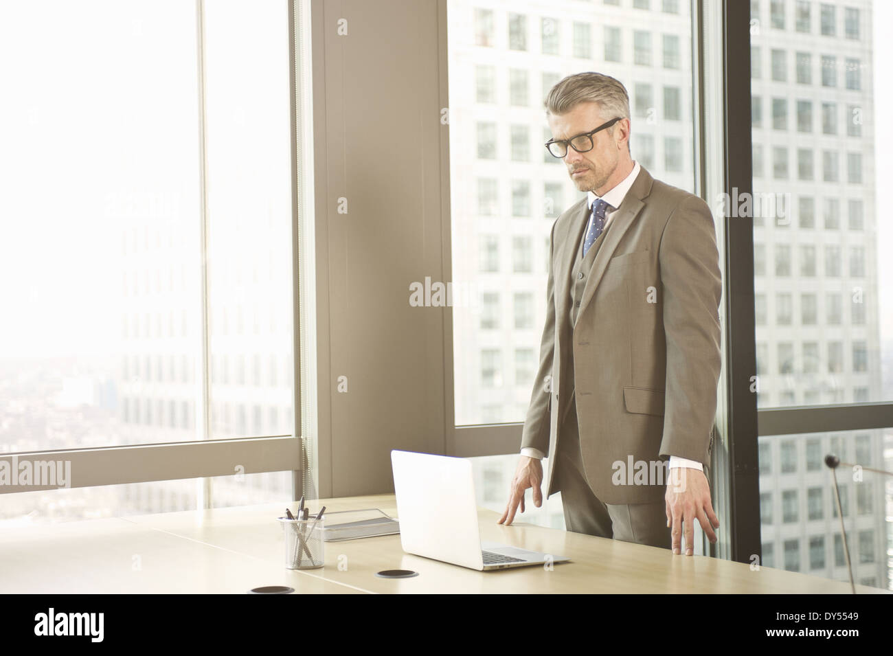 Businessman looking down at laptop on office desk - Stock Image