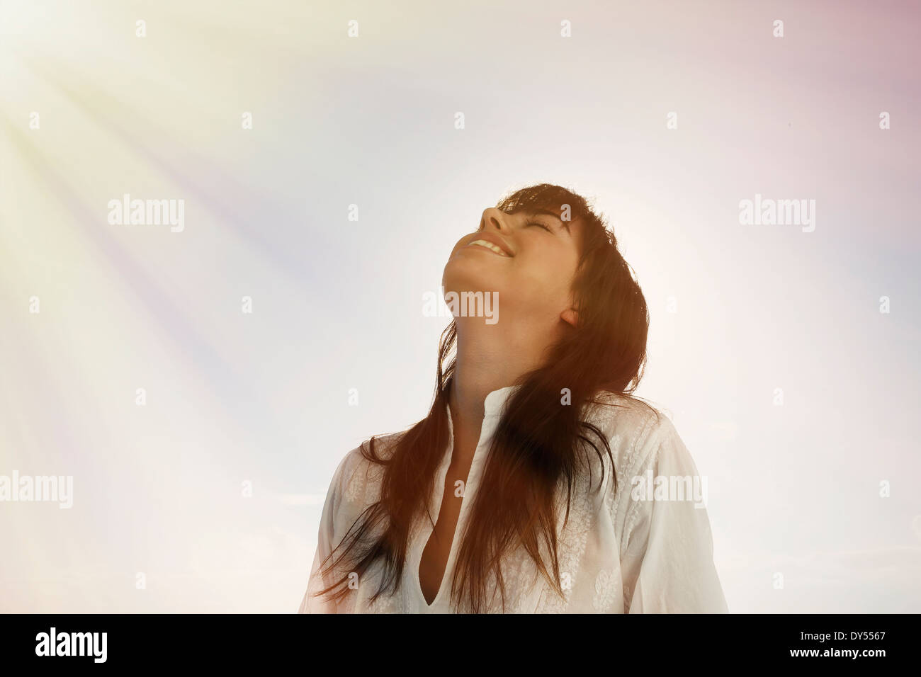 Young woman looking up, sun beams on face - Stock Image