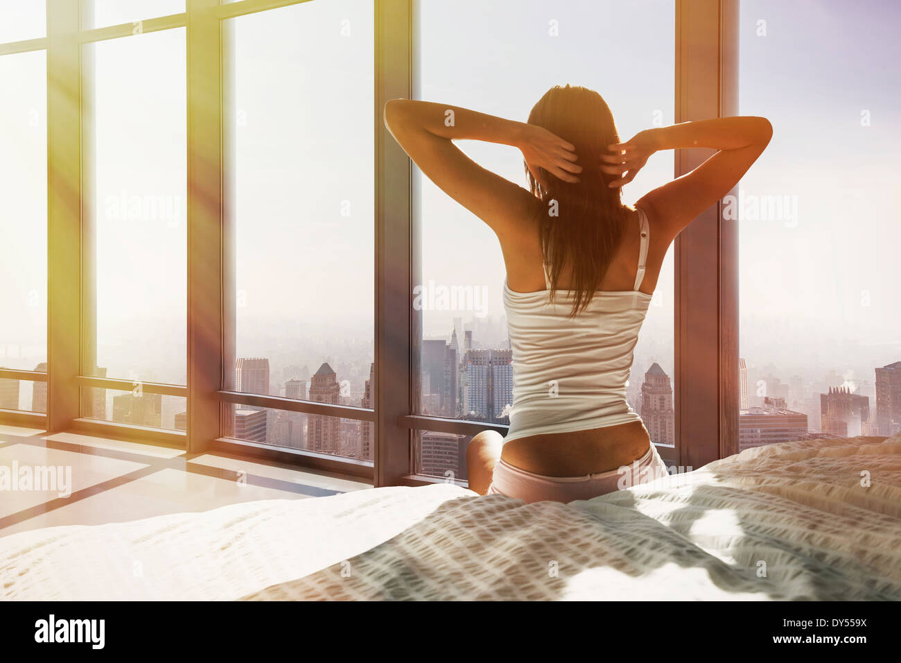Young woman sitting on bed, stretching, overlooking city - Stock Image