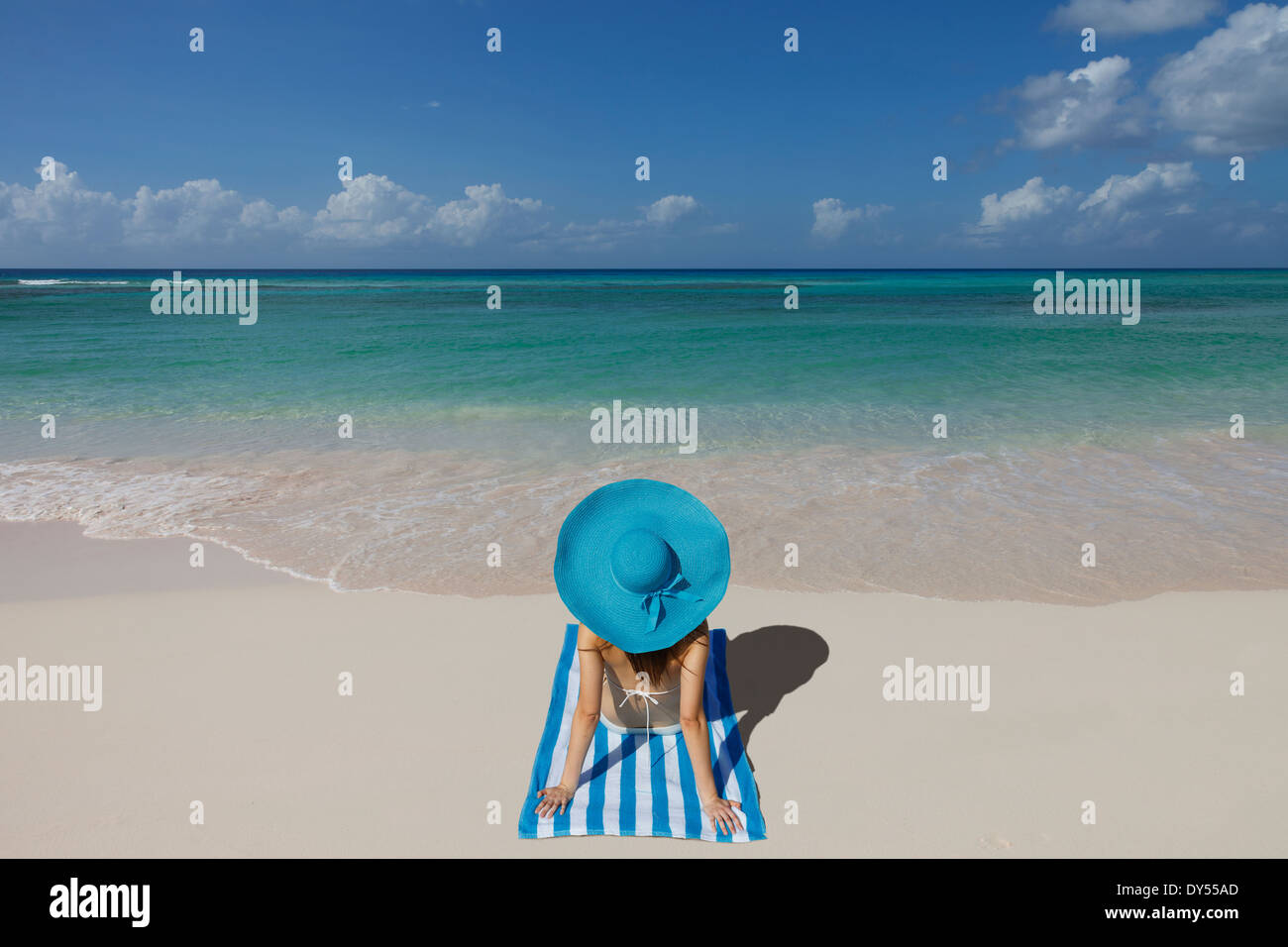 Young woman relaxing on beach with blue sunhat - Stock Image