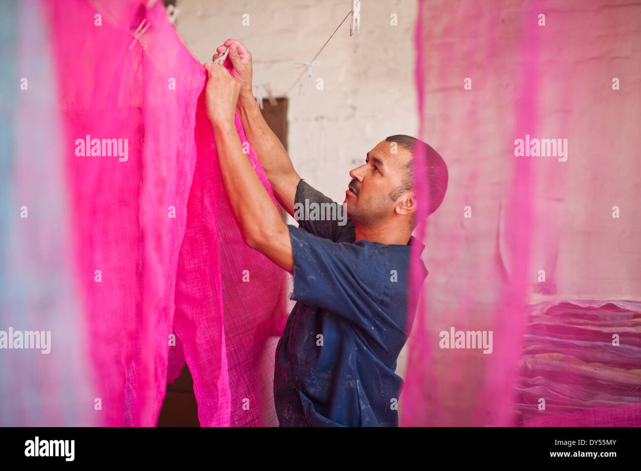 Man hanging up dyed fabric in traditional milliners workshop - Stock Image