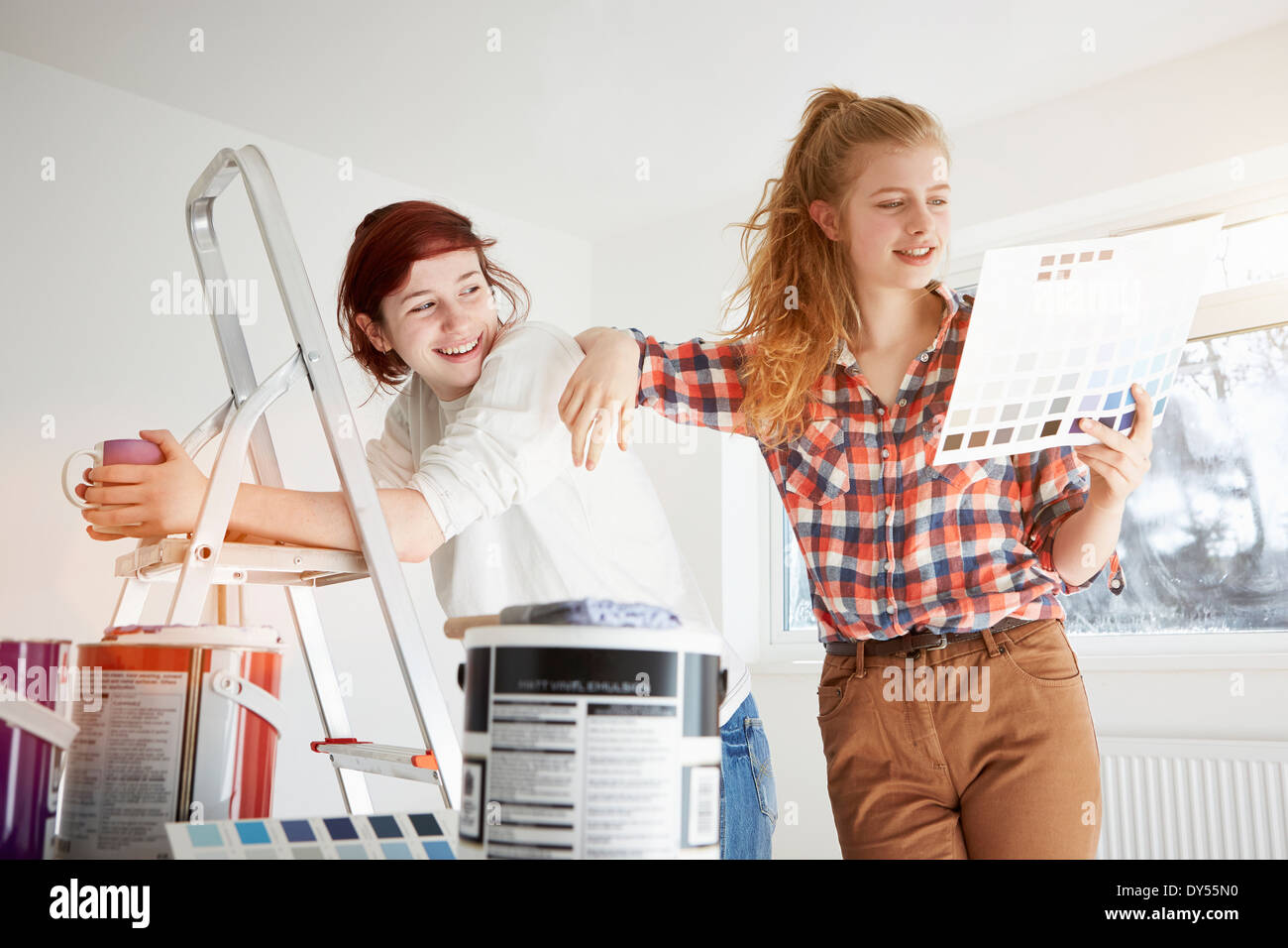 Two teenage sisters preparing to decorate bedroom - Stock Image