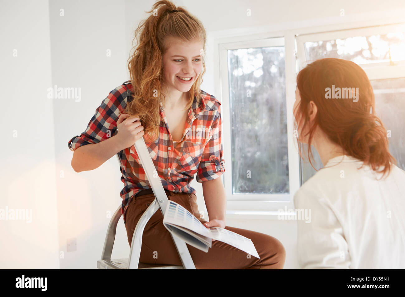 Two teenage sisters discussing color swatches for bedroom - Stock Image