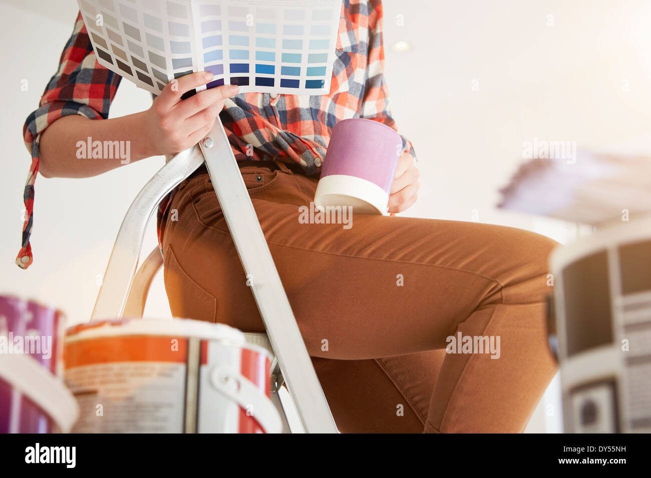 Teenage girl sitting on stepladders with coffee and swatch - Stock Image