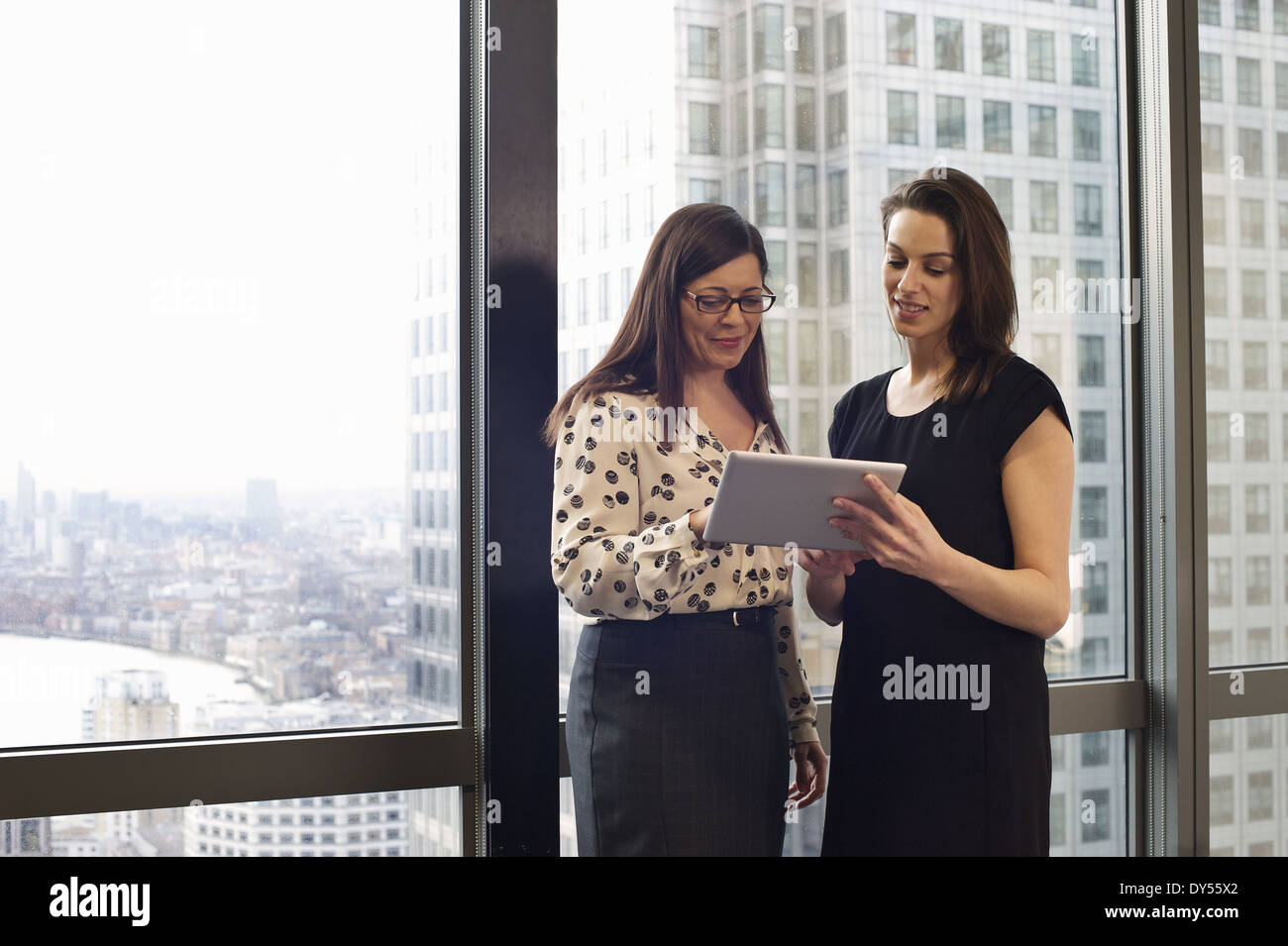 Female business colleagues looking at digital tablet in office - Stock Image