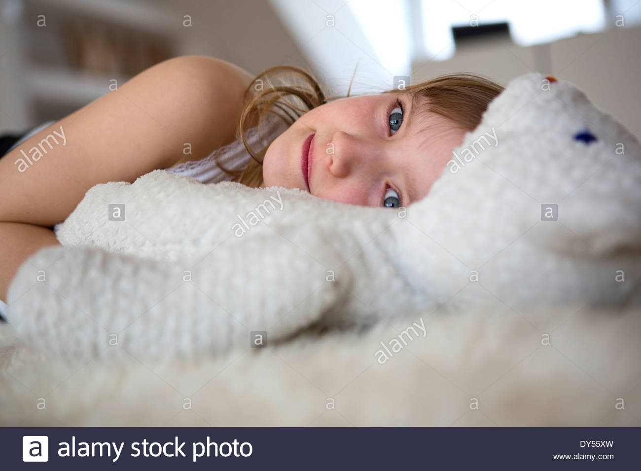 Girl lying on furry bed with teddy bear - Stock Image
