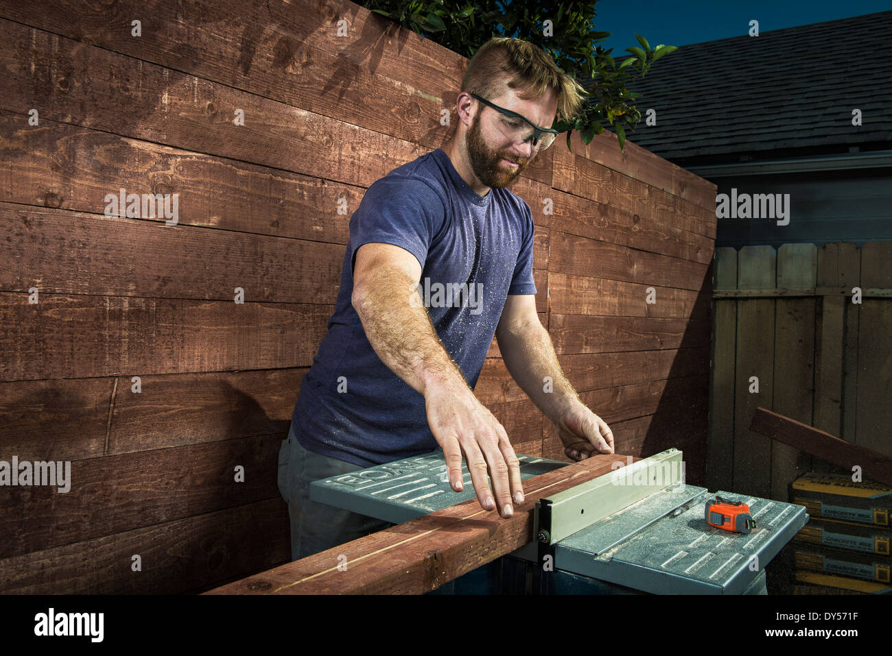 Joiner in backyard lining up planks of wood on workbench Stock Photo