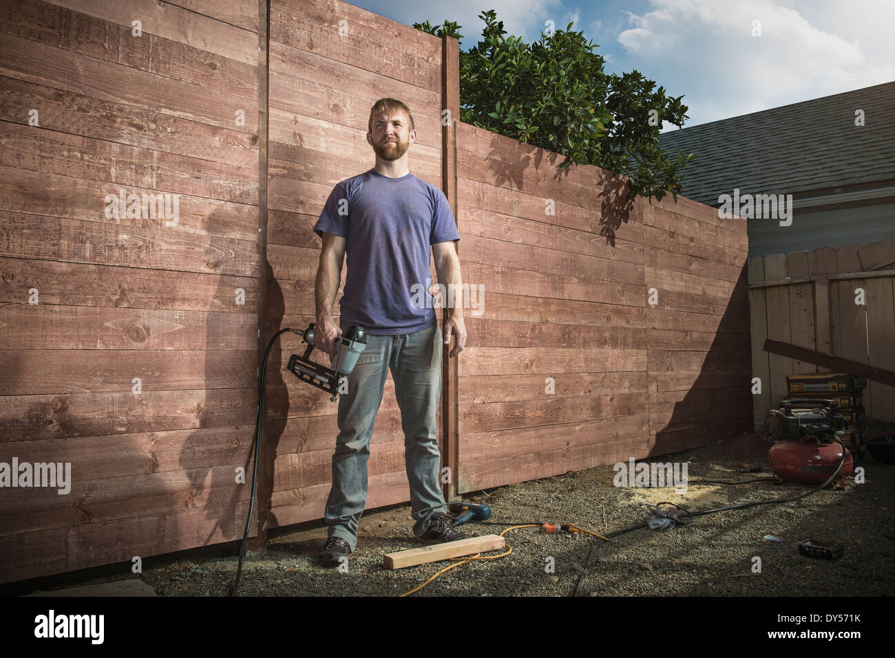 Portrait of joiner in backyard in front of new fence - Stock Image