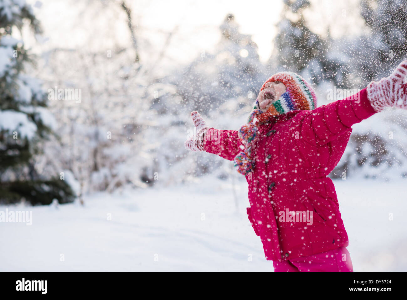Young girl shouting and throwing snow mid air - Stock Image
