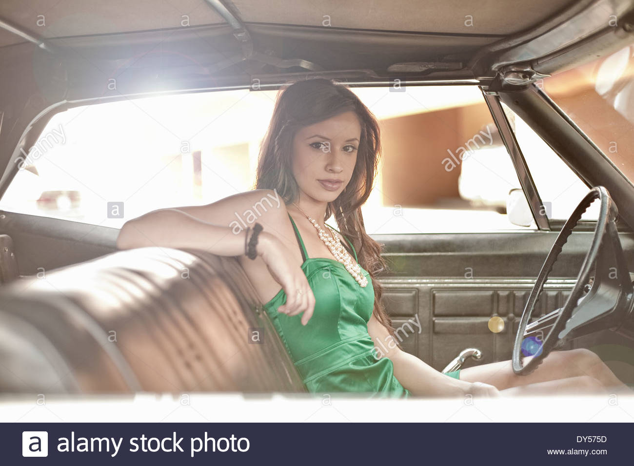 Portrait of sultry young woman waiting in car - Stock Image