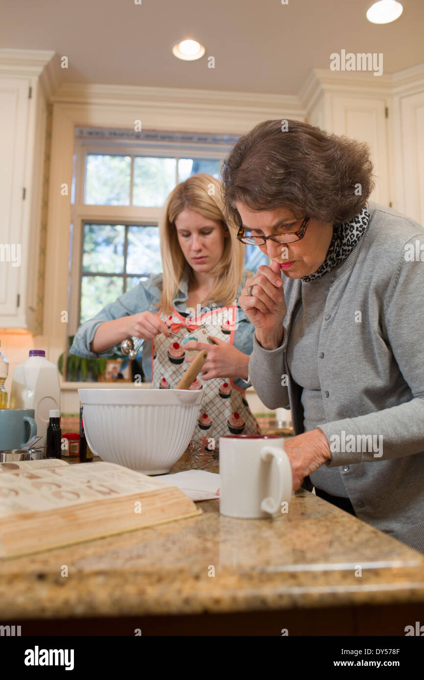 Senior woman and granddaughter pouring baking in kitchen - Stock Image