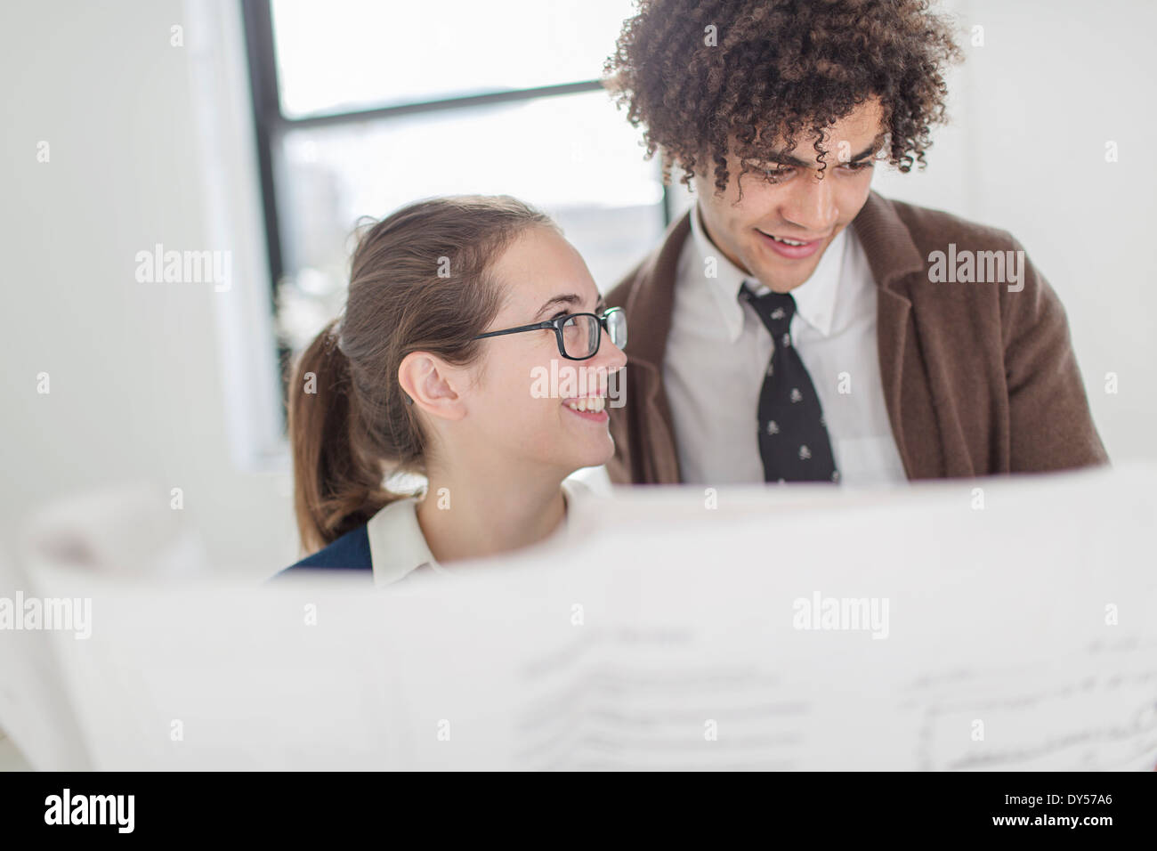 Two colleagues discussing blueprint - Stock Image