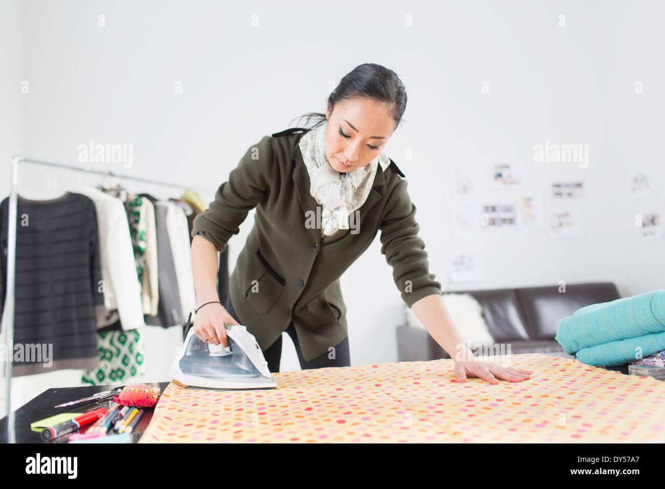 Female fashion designer ironing fabric - Stock Image