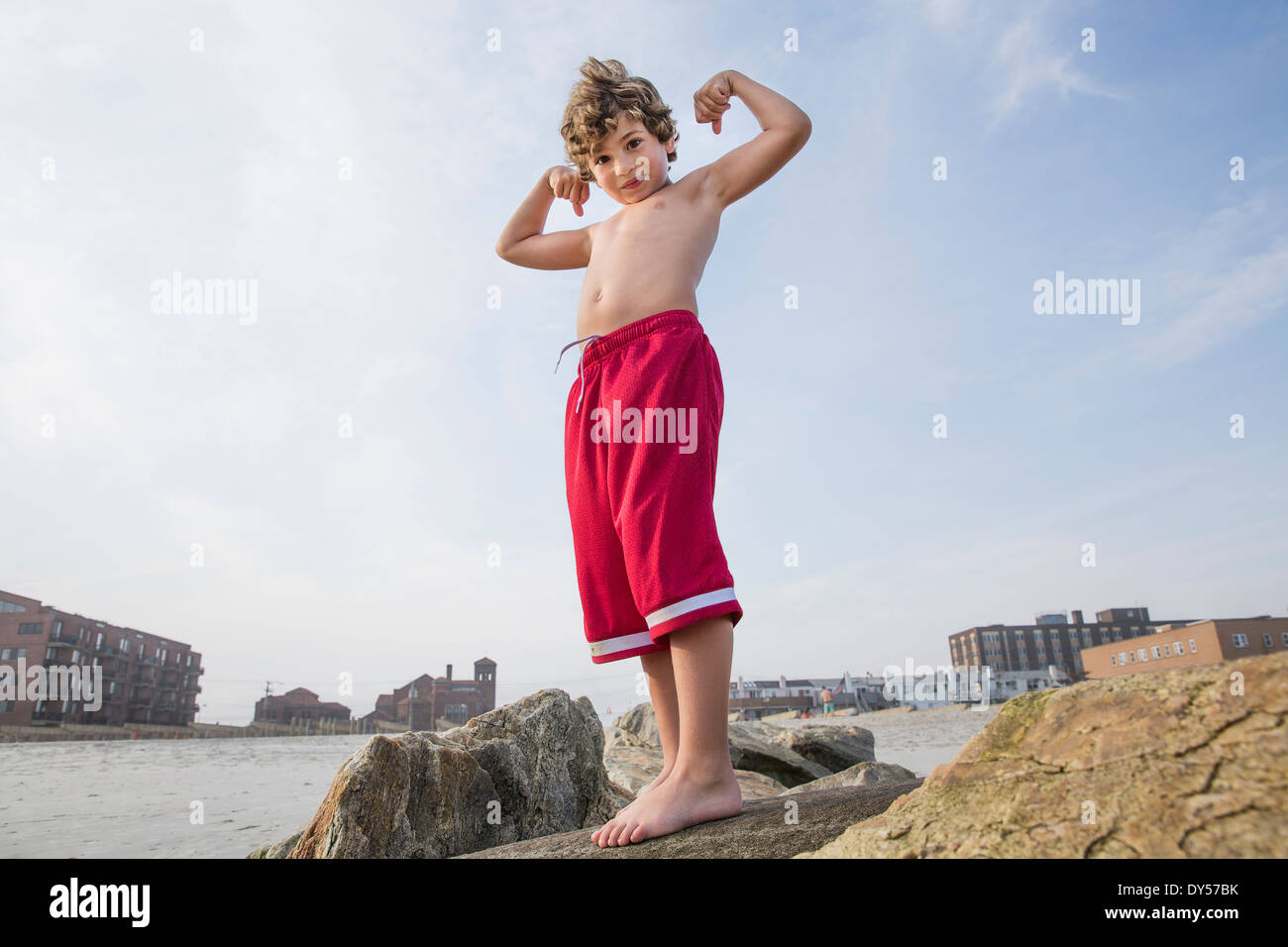 Boy at the coast showing off his arm muscles, Long Beach, New York State, USA - Stock Image