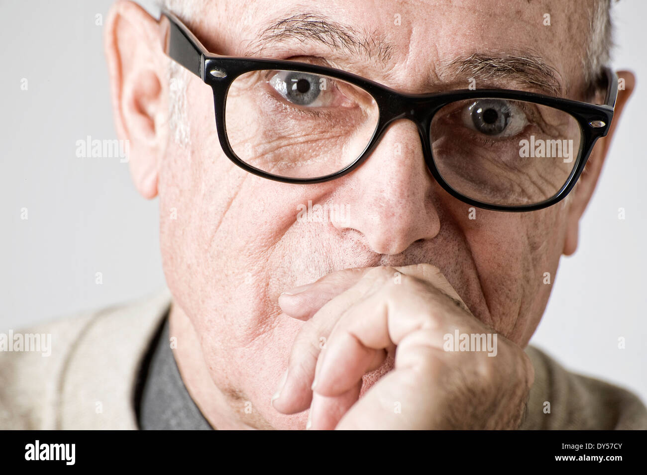 Portrait of senior man, hand on mouth Stock Photo