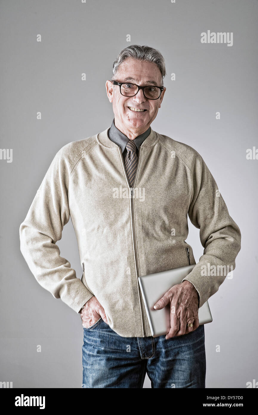 Portrait of senior man, hand in pocket, holding bag - Stock Image
