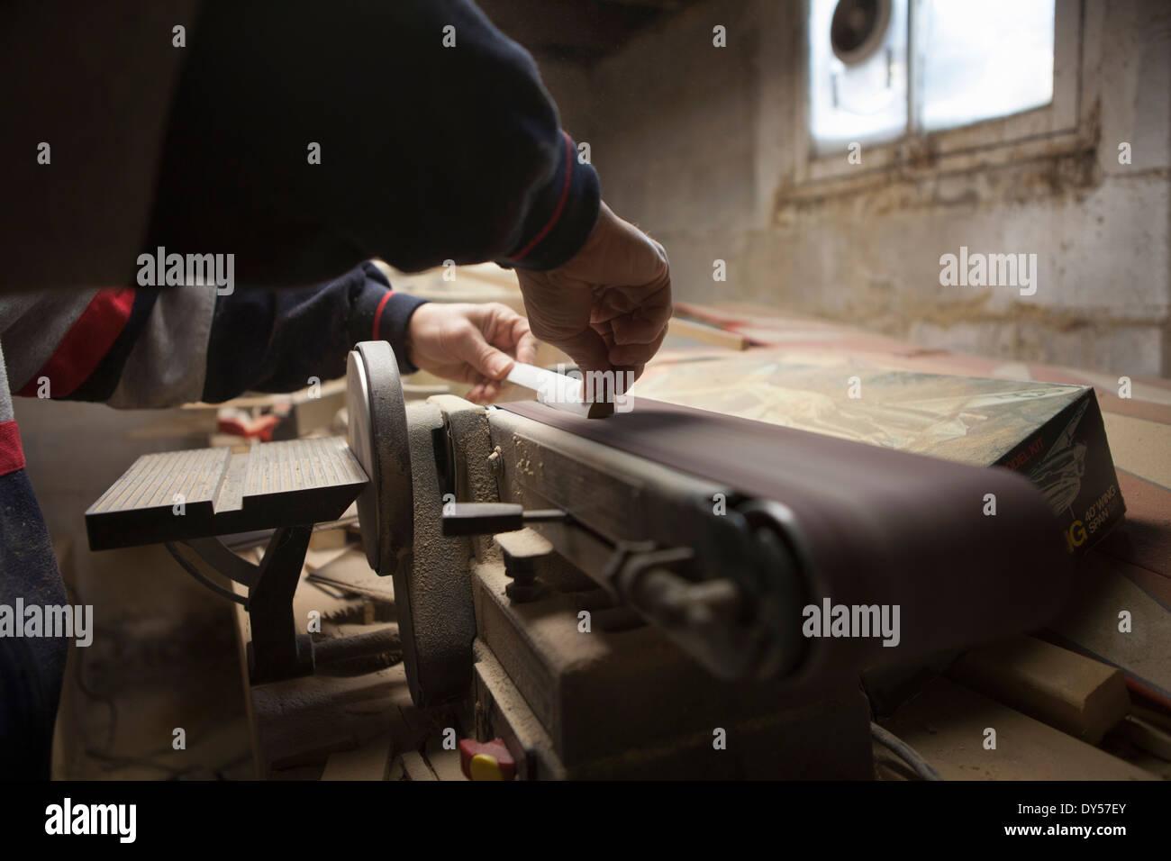 Close up of mature man using sanding belt in workshop - Stock Image