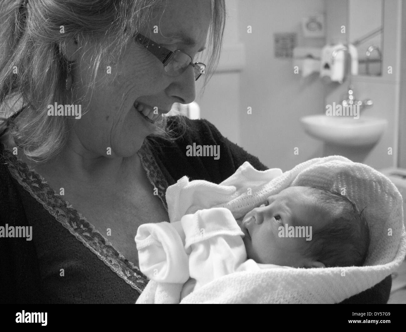 Black and white shot of a grandmother holding her newborn baby granddaughter - Stock Image