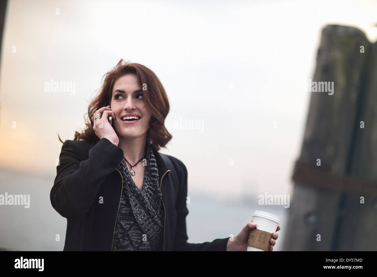 Young woman with cellphone and coffee next to Hudson river, New York, USA - Stock Image