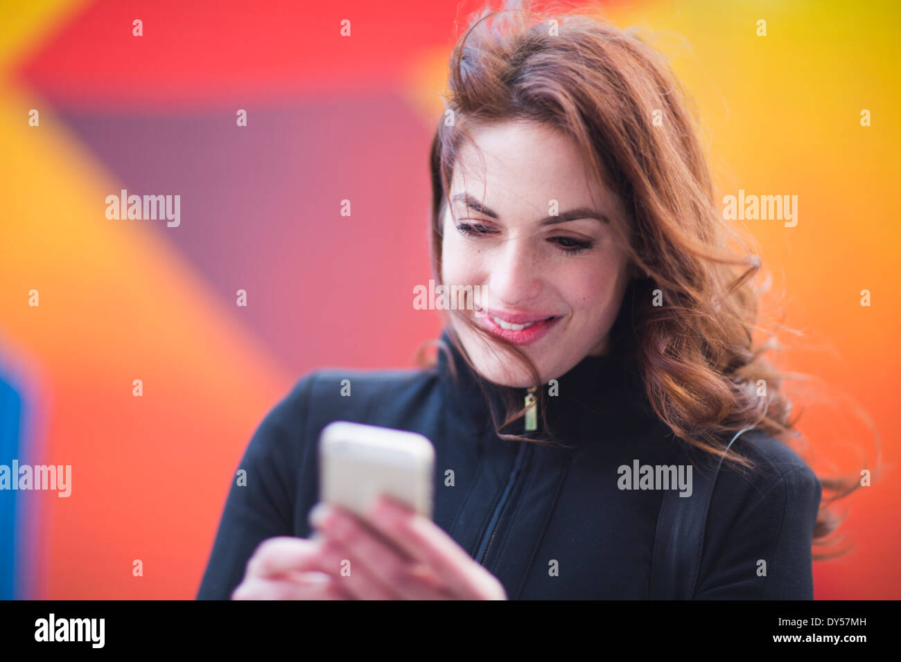 Young woman reading text messages on city street - Stock Image