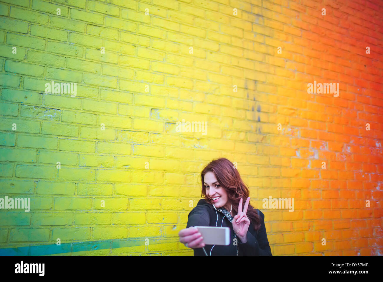 Young woman taking self portrait next to yellow wall - Stock Image