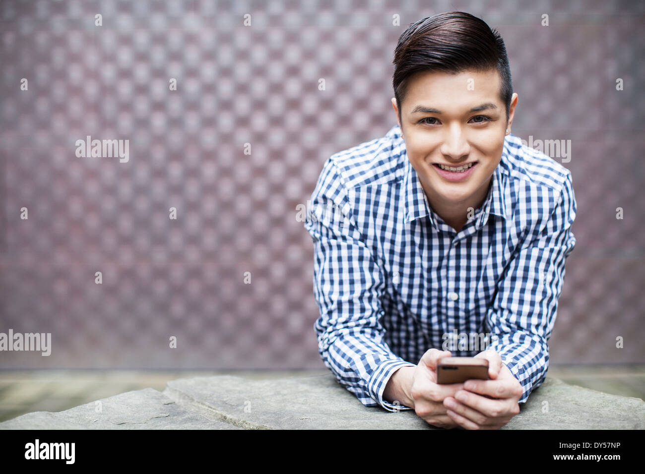 Portrait of young man holding smartphone - Stock Image