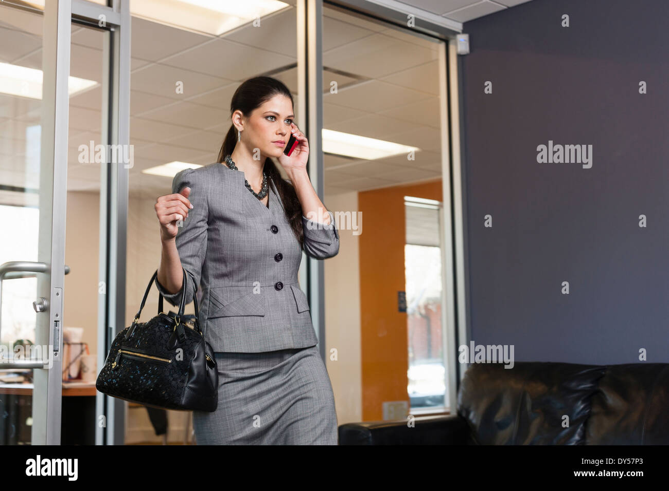 Young businesswoman leaving office, on phonecall - Stock Image
