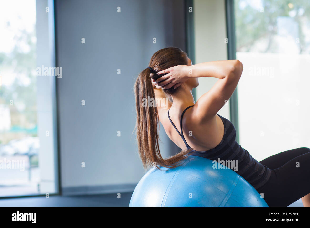 Young woman working out with gym ball - Stock Image
