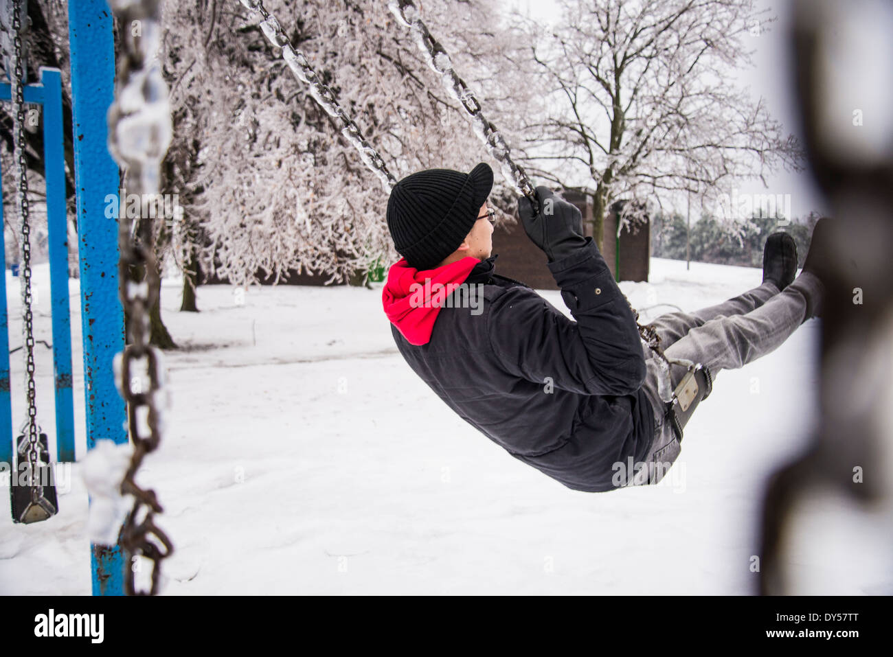 Young man playing on park swing at -30 degrees celcius - Stock Image