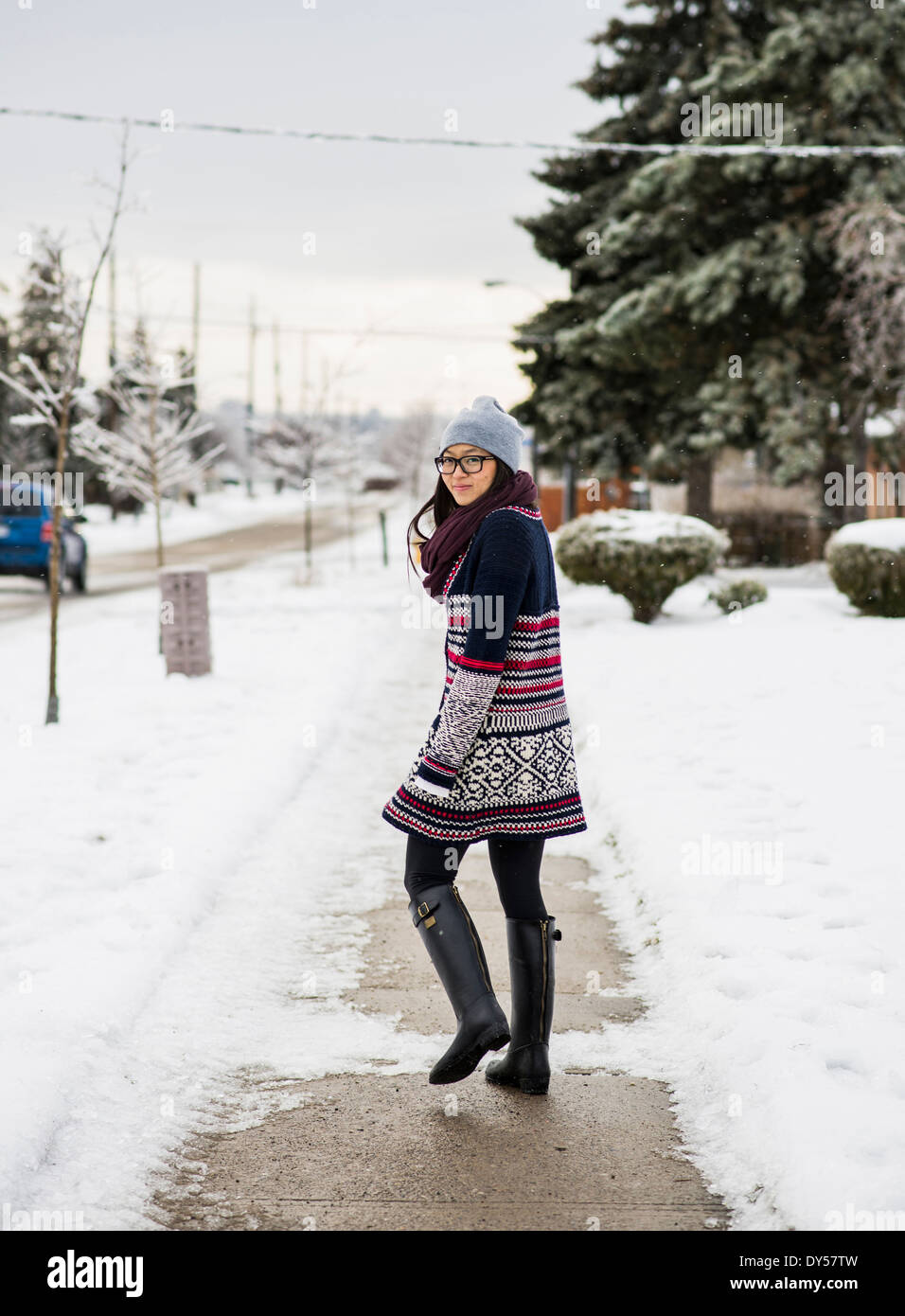 Young woman walking down snow covered street - Stock Image
