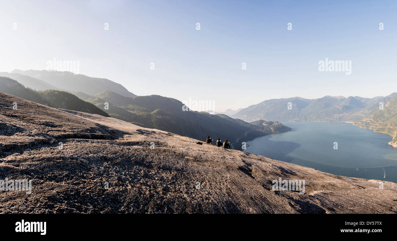 Three young female hikers taking a break on rock, Squamish, British Columbia, Canada - Stock Image