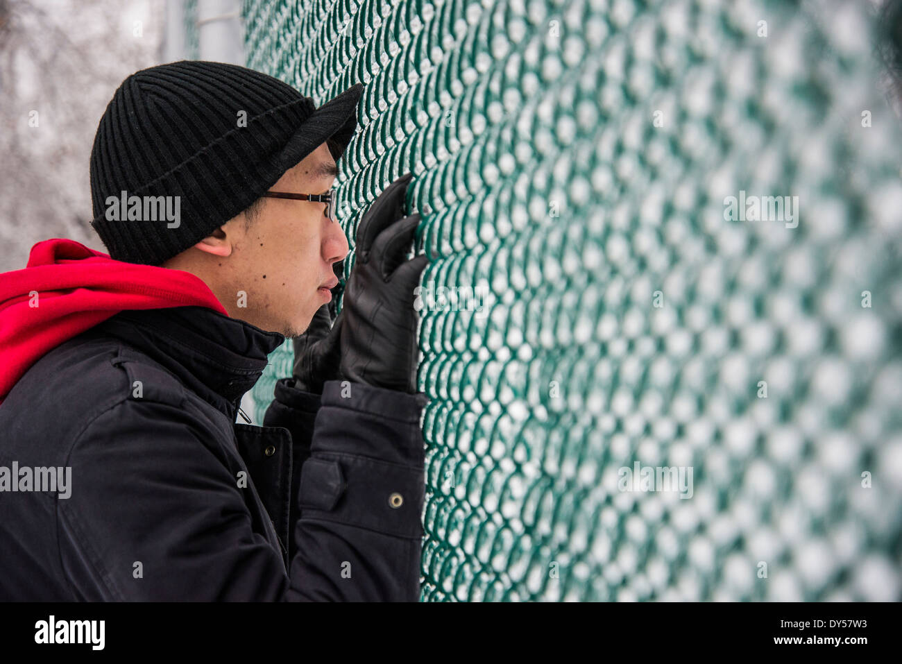 Portrait of young man looking through park fence at -30 degrees celcius - Stock Image