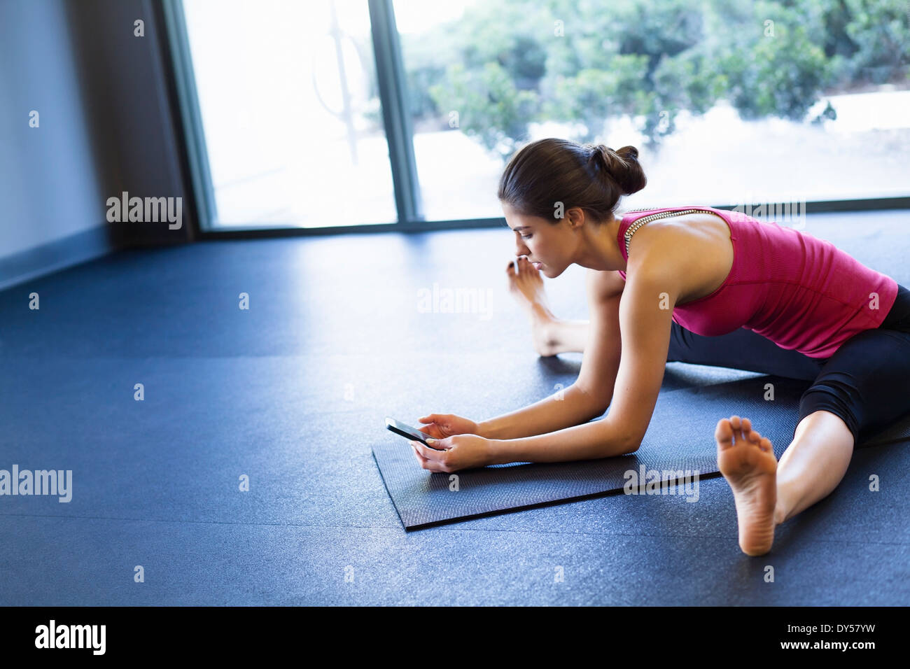 Young woman in yoga posture using cellular phone - Stock Image