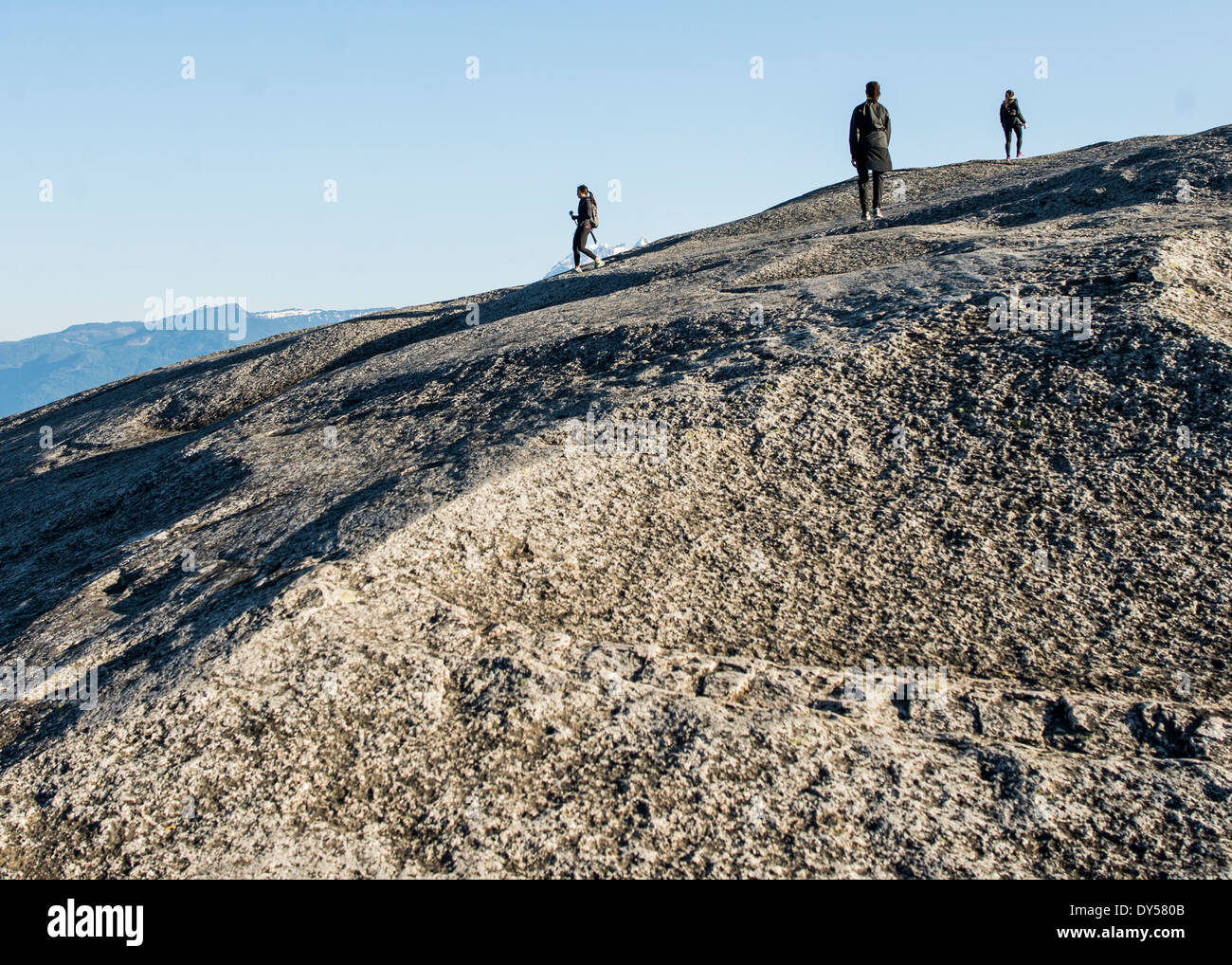 Three young female hikers on rock, Squamish, British Columbia, Canada - Stock Image